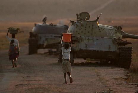 Angolanos pasan al lado de tanques cubanos abandonados en Longa, en ruta a Cuito Cuanavale, en el 2008